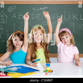 clever kids student group at school classroom raising hand as smart children - Stock Photo