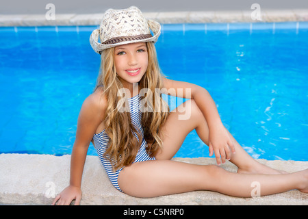 blond children girl sittin in swimming pool border in summer vacation - Stock Photo