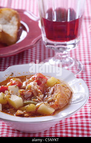 Basque fish soup wot a glass of red wine behind - Stock Photo
