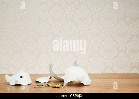 Smashed piggy bank and coins - Stock Photo