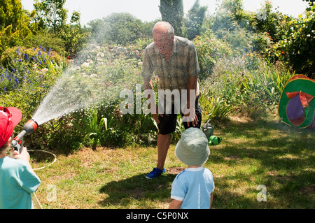 Grandsons spraying grandfather with hosepipe - Stock Photo