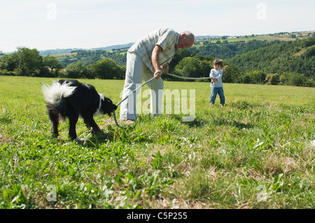 Grandfather and grandsons playing tug of war in field - Stock Photo
