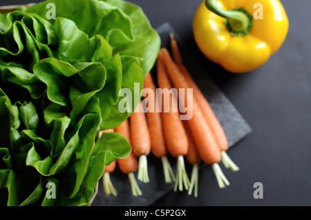 Carrots and one yellow sweet pepper bell with lettuce - Stock Photo