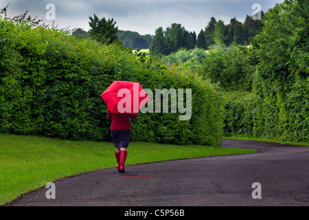 Photo of a woman walking down a road holding a red umbrella after a heavy downpour of rain on an overcast day. - Stock Photo
