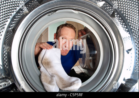 man putting dirty socks into washing machine - Stock Photo