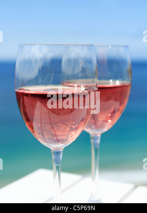 Glasses of rosé wine by the ocean - Stock Photo