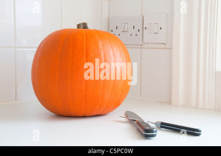 A pumpkin and two knives - Stock Photo