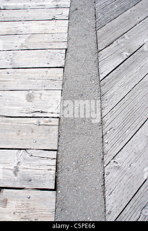 Weatherbeaten wooden walkway laid out in an interesting pattern divided by a cement barrier - Stock Photo