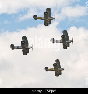 Four vintage bi-planes flying in formation, Duxford air show 2011 - Stock Photo