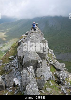 A female hill walker scrambling on the Crib Lem spur of Carnedd Dafydd in the Carneddau mountains, Snowdonia - Stock Photo