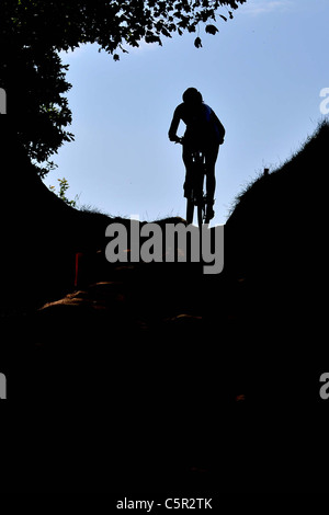 A rider goes up a hill in the forest. Silhouette. Womens Race. Hadleigh Farm Mountain Bike International. London - Stock Photo