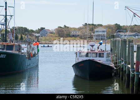 Lobster boats sit idle as kayaks drift by the wharf in Old Westport, Massachusetts. - Stock Photo