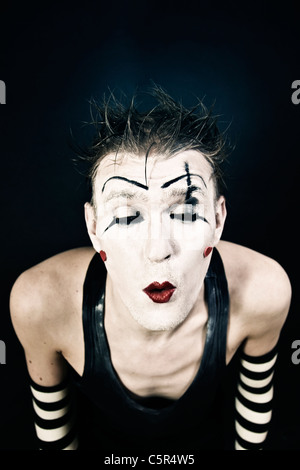 Studio portrait of a terrible clown with a dark makeup on black background - Stock Photo