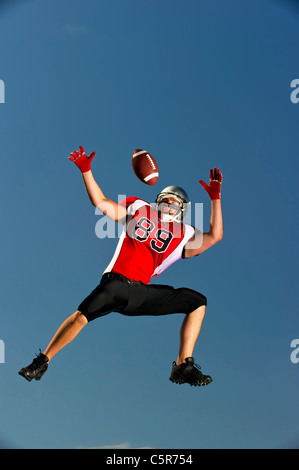 American Football player leaps to make catch. - Stock Photo