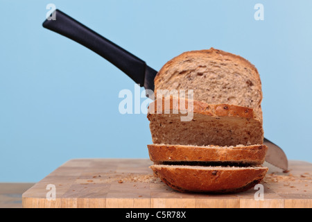 Photo of a wholemeal loaf of bread being sliced with a knife. - Stock Photo