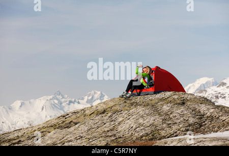 A women camping in high snowy mountains drinking liquid to re-hydrate. - Stock Photo