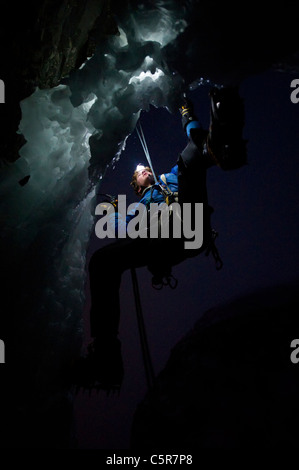 Ice Climbing at night on the edge of a cave. - Stock Photo