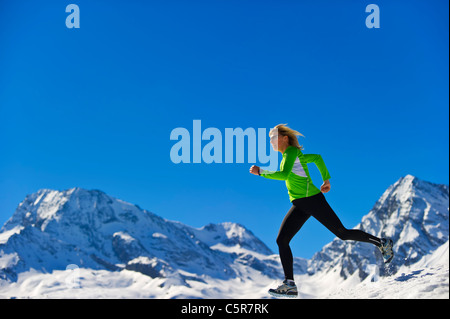 A woman jogging fast over snowy mountains. - Stock Photo