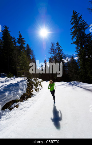 A girl jogging at high altitude in snowy mountains. - Stock Photo