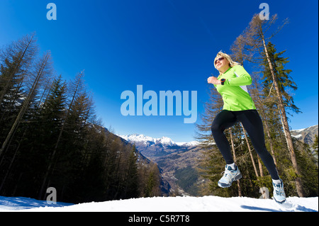 A woman jogging in snowy mountains. - Stock Photo