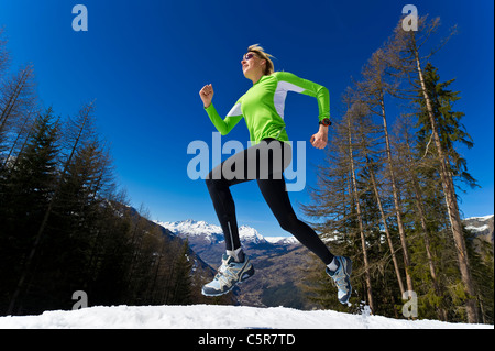 A woman jogging through snowy winter mountains. - Stock Photo