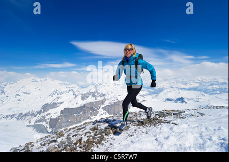 Women enjoying a run across a snowy alpine mountain range. - Stock Photo