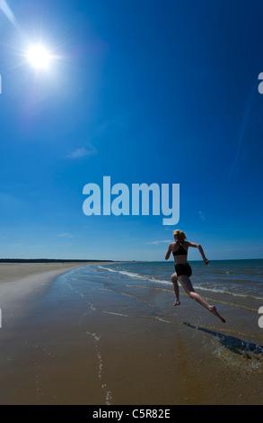 A jogger splashing along the ocean beach. - Stock Photo