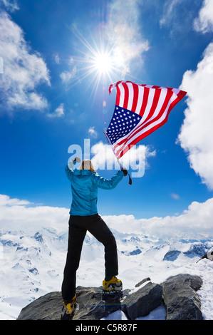 Mountaineer celebrates on summit. - Stock Photo