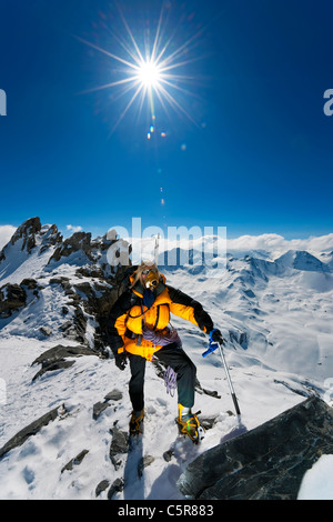 A mountaineer on climb to summit of snowy mountain high above the clouds, summits and peaks. - Stock Photo