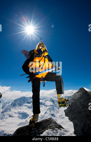 A mountaineer climbs over rocks on very high snowy mountain above the clouds. - Stock Photo