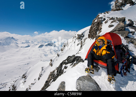 A mountaineer sitting in tent with oxygen mask looks out over high snowy mountains. - Stock Photo