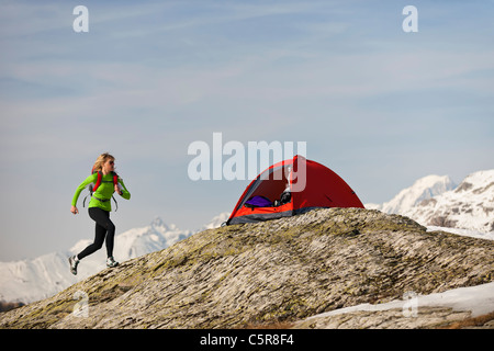 A woman runs back to her tent in high altitude mountains. - Stock Photo