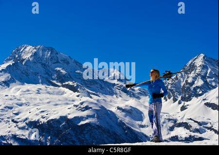 A women takes in the breathtaking snowy mountain view. - Stock Photo