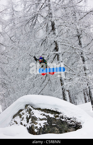 A snowboarder jumping high in a snowy forest. - Stock Photo