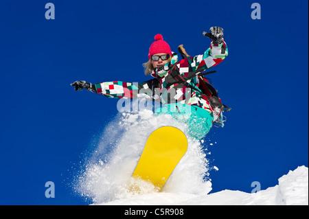 A female snowboarder riding hard through deep fresh powder snow. - Stock Photo