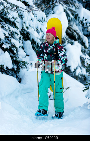 A snowboarder hiking up the mountain in snowshoes to ride the back country. - Stock Photo