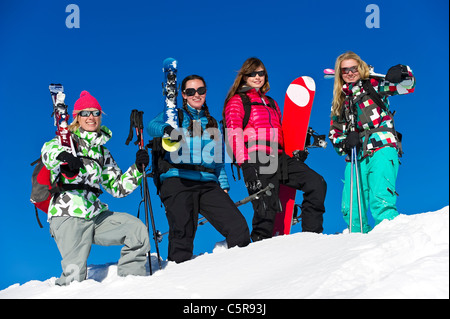 Four friends on a skiing and snowboarding holiday having fun. - Stock Photo