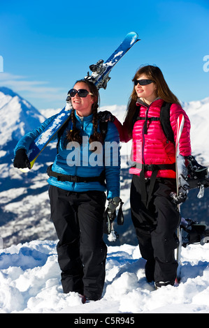 A skier and snowboarder having fun in the snowy mountains. - Stock Photo