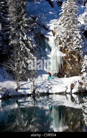 Snowshoeing around a stunning winter Alpine mountain lake - Stock Photo