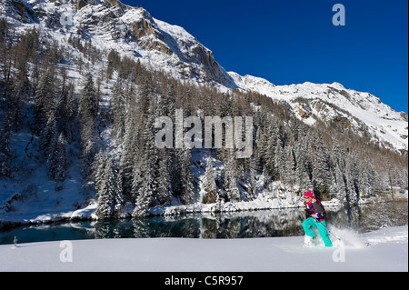 A woman running through deep powder snow on snow shoes past stunning snowy mountains and lake. - Stock Photo