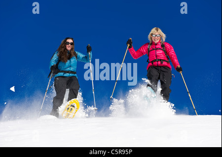 Two friends snowshoeing race each other for fun. - Stock Photo