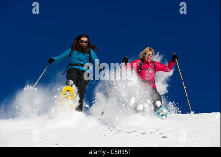 Two friends snowshoeing run through deep fresh powder snow. - Stock Photo