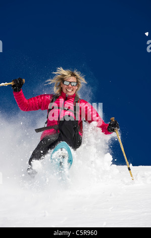 A woman having fun snowshoeing through deep fresh powder snow. - Stock Photo