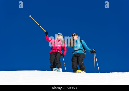 Two friends having fun snowshoeing - Stock Photo