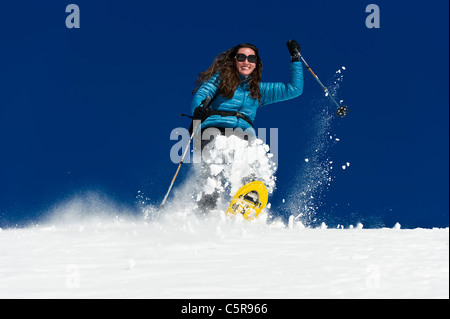 A woman having fun snowshoeing down a deep fresh snow field. - Stock Photo