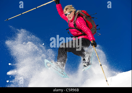 A woman snowshoeing leaps through fresh powder snow. - Stock Photo