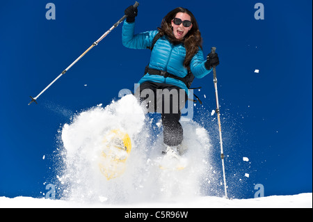 A woman snowshoeing and having fun in fresh powder snow. - Stock Photo