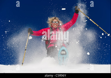 Snowshoeing in deep fresh powder and having fun. - Stock Photo