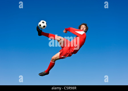 A soccer player volleys the ball. - Stock Photo