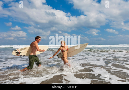 Two surfers having fun in the waves. - Stock Photo